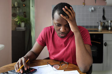 Young anxious worrying african american man looks desperately to bills, faces problems with paying taxes, holding head with one hand