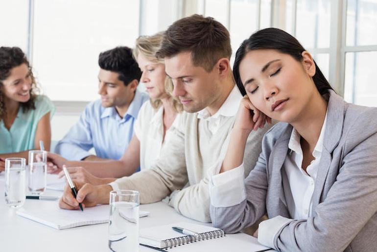 Casual businesswoman falling asleep during meeting