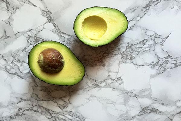 Split open avocado on marble